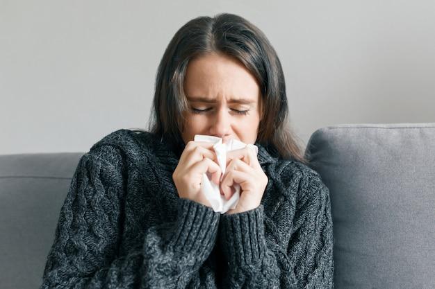 Ragazza a casa in caldo maglione lavorato a maglia con fazzoletto, starnutisce Foto Premium