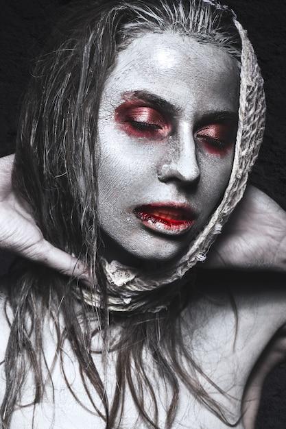 Ragazza a forma di zombi, cadavere di halloween con sangue sulle labbra Foto Premium