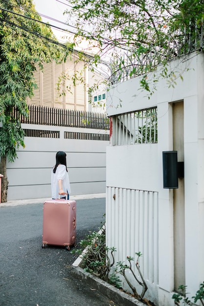Ragazza a piedi con i bagagli rosa Foto Gratuite