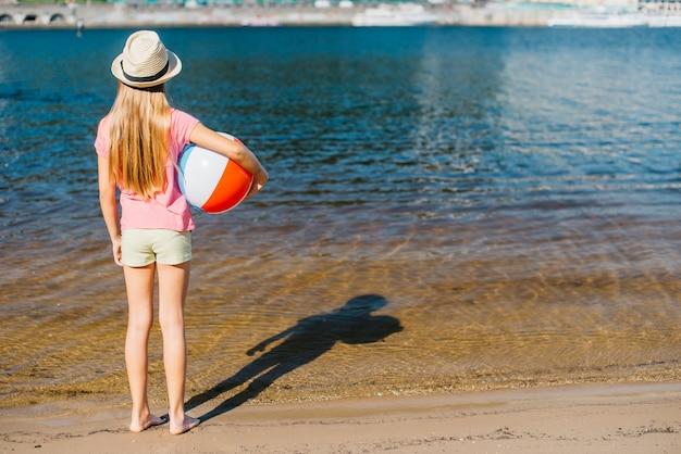 Ragazza a piedi nudi con palla a vento guardando acqua Foto Gratuite