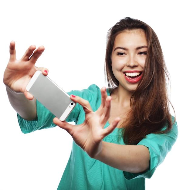 Ragazza abbastanza teenager che prende i selfie Foto Premium