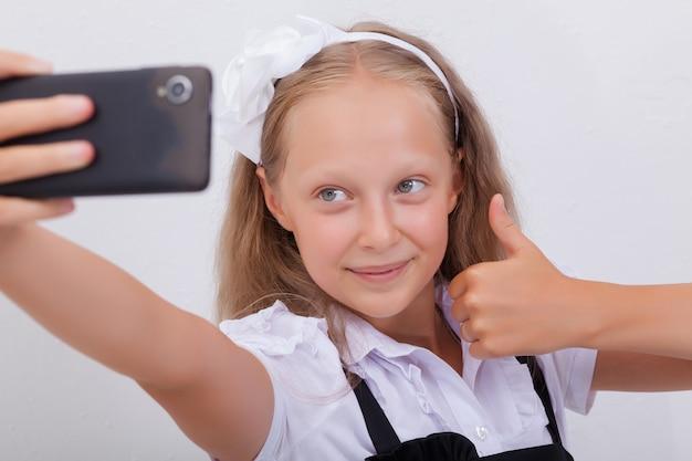 Ragazza abbastanza teenager che prende i selfies con il suo smartphone Foto Gratuite