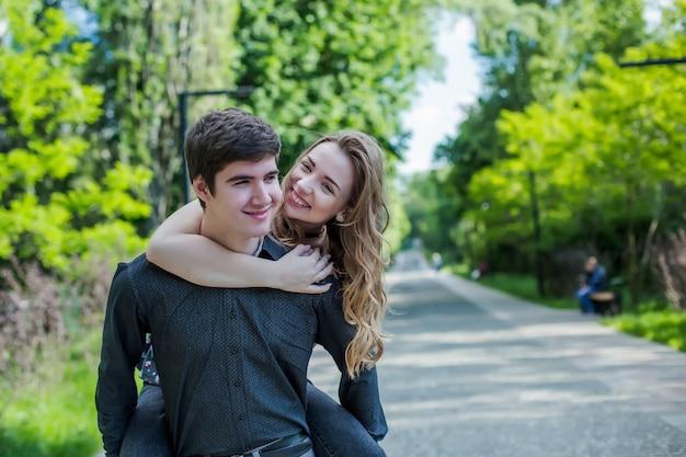 Ragazza abbraccia il ragazzo da dietro. coppia felice a piedi Foto Premium