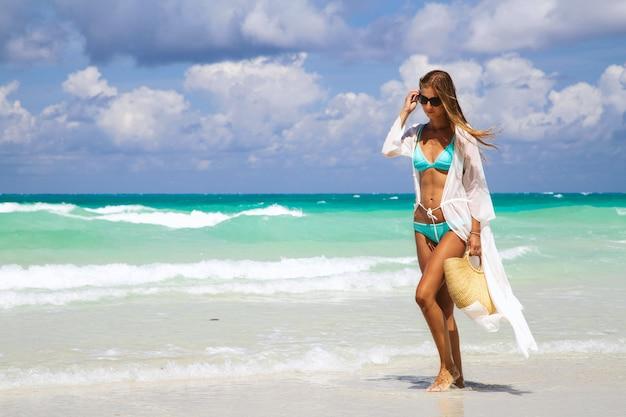 Ragazza abbronzata in bikini blu e tunica bianca che tiene la borsa di paglia alla moda e camminare in riva al mare. Foto Premium