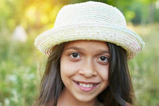 Ragazza adolescente in un cappello in un campo al tramonto Foto Premium