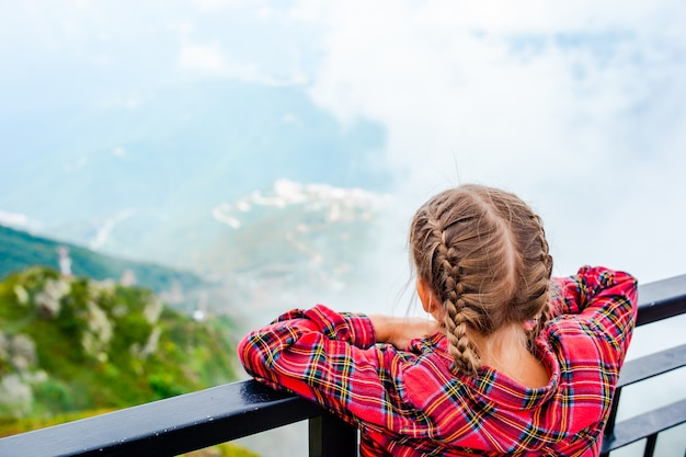Ragazza adorabile che esamina le montagne Foto Premium