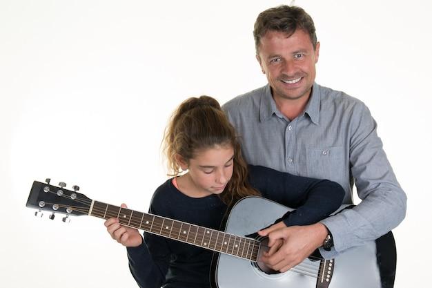 Ragazza adorabile che ottiene le lezioni di chitarra con l'uomo Foto Premium