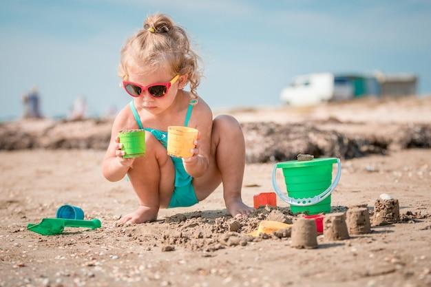 Ragazza adorabile del bambino che gioca sulla spiaggia di sabbia bianca Foto Premium