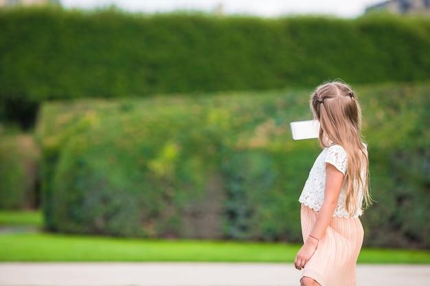 Ragazza adorabile del bambino con il telefono a parigi durante la vacanza europea Foto Premium