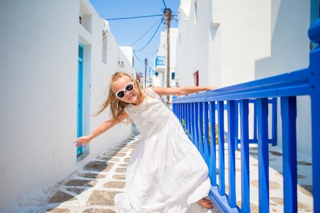 Ragazza affascinante in vestito bianco all'aperto in vecchie strade un mykonos. scherzi alla via del villaggio tradizionale greco tipico con le pareti bianche e le porte variopinte sull'isola di mykonos, in grecia Foto Premium