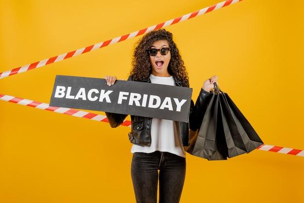 Ragazza africana emozionante con i sacchetti della spesa neri del segno e della carta di venerdì isolati sopra giallo con nastro adesivo Foto Premium