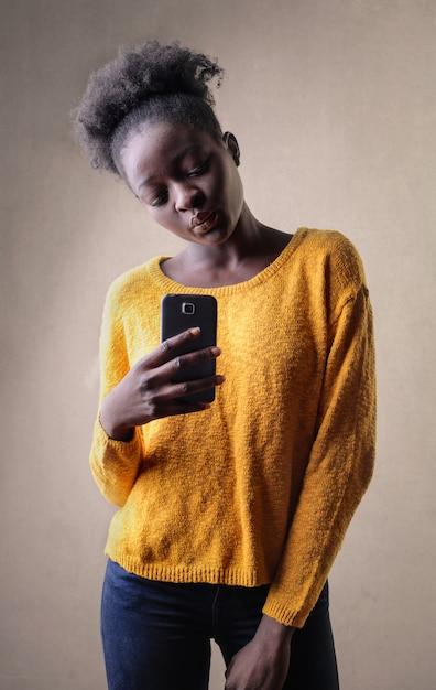 Ragazza afro prendendo una foto con il suo smartphone Foto Premium