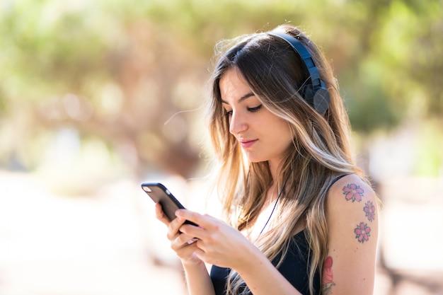 Ragazza all'aperto in un parco che ascolta la musica con il cellulare Foto Premium
