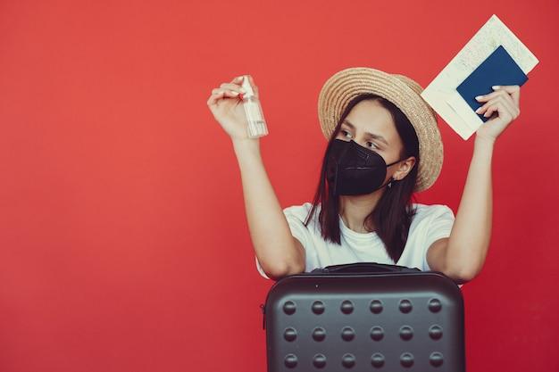 Ragazza alla moda che posa con l'attrezzatura di viaggio su una parete rossa Foto Gratuite