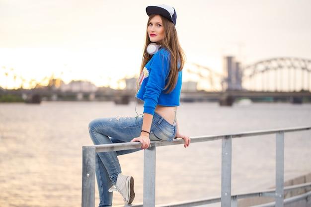 Ragazza alla moda che si siede su un corrimano Foto Gratuite