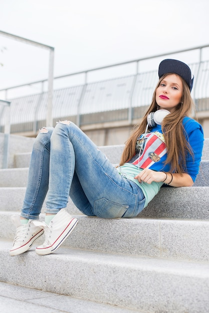 Ragazza alla moda che si siede sui gradini Foto Gratuite