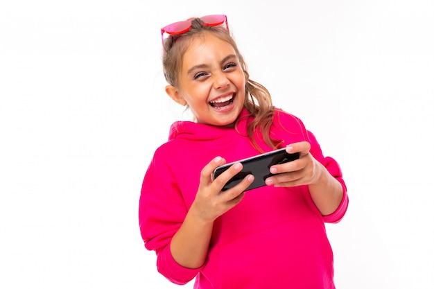 Ragazza alla moda in felpa rosa, occhiali da sole rosa è felice e sorride, comunica con gli amici o la famiglia isolata sulla superficie bianca Foto Premium