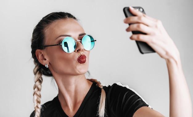 Ragazza alla moda in occhiali da sole con occhiali colorati fa selfie al telefono Foto Premium