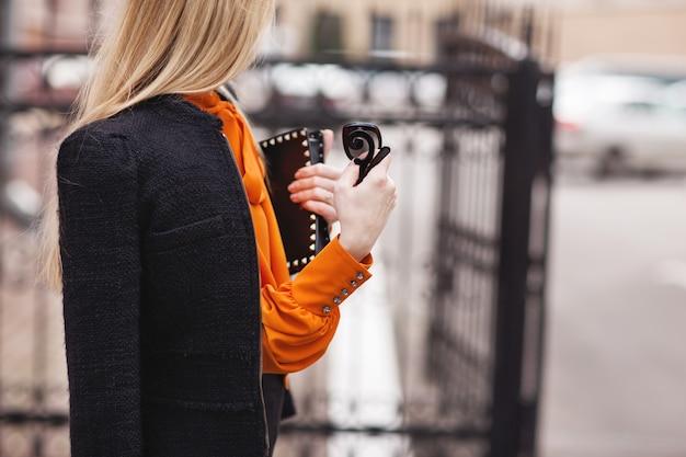 Ragazza alla moda in un abito nero e blusa arancione si trova vicino al recinto Foto Premium