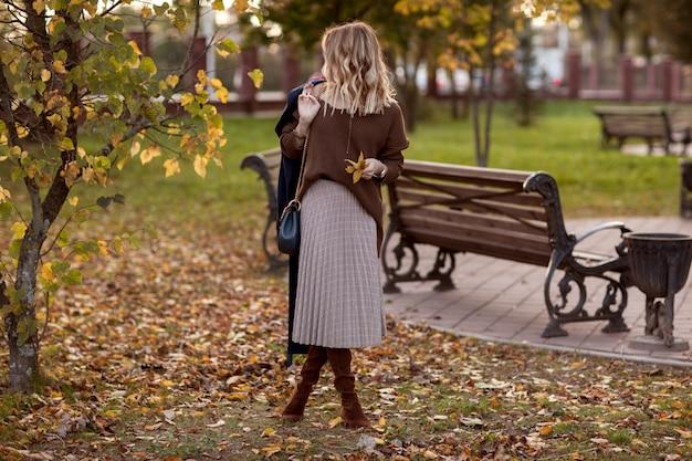 Ragazza alla moda in un parco in autunno in un maglione marrone e gonna scozzese. Foto Premium