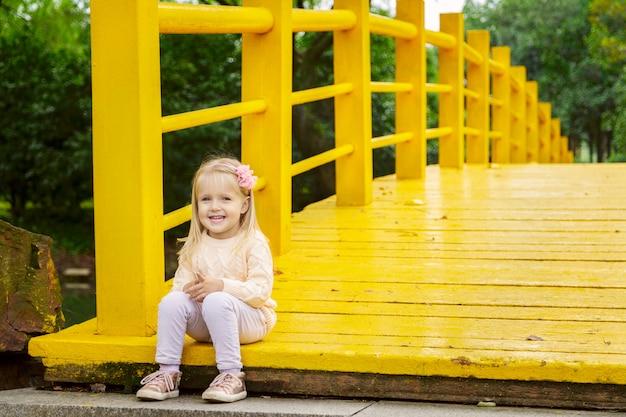 Ragazza alla moda llittle su un ponte giallo nel parco Foto Premium
