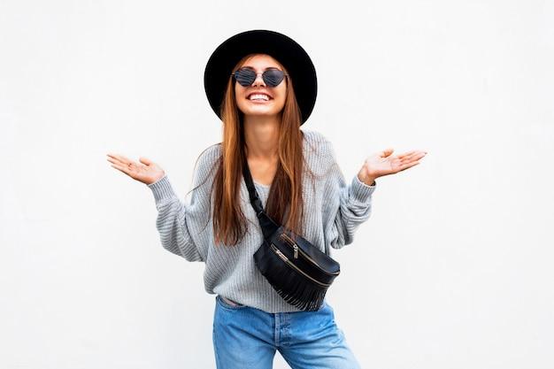 Ragazza alla moda uscita riuscita con il sorriso schietto che posa sulla parete urbana bianca Foto Gratuite