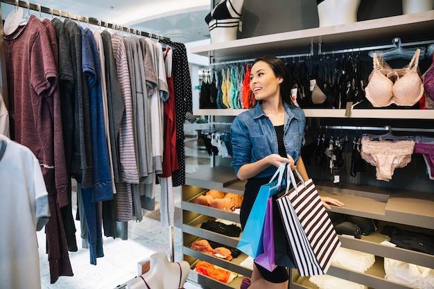 f5a415677a47 Ragazza allegra camminare in negozio di abbigliamento Foto Gratuite
