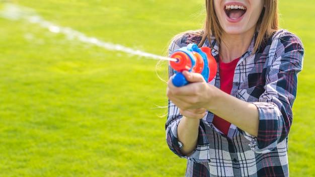 Ragazza allegra che gioca con la pistola ad acqua Foto Gratuite