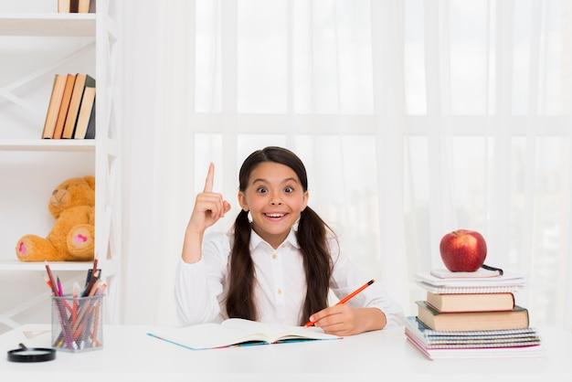 Ragazza allegra facendo i compiti con gioia Foto Gratuite