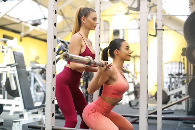 Ragazza allenamento in palestra con un personal trainer Foto Premium