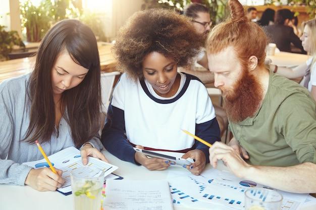Ragazza asiatica che compila documenti con grafici e diagrammi mentre la donna africana condivide idee con un collega barbuto dai capelli rossi sul touch pad. Foto Gratuite