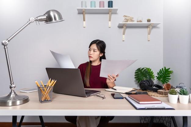 Ragazza asiatica che lavora a distanza da casa Foto Premium
