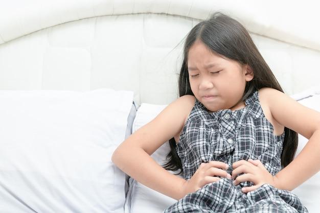 Ragazza asiatica che soffre di mal di stomaco Foto Premium