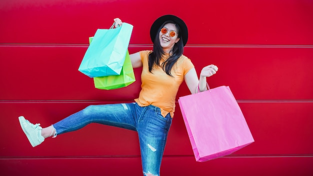 Ragazza asiatica d'avanguardia felice con i sacchetti della spesa all'aperto. giovane donna divertirsi comprando nuovi vestiti e accessori Foto Premium