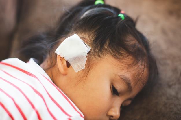 Ragazza asiatica del bambino ferita all'orecchio. l'orecchio del bambino con la benda dopo che è stata un incidente. Foto Premium