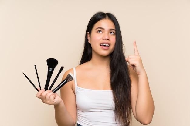 Ragazza asiatica del giovane adolescente che tiene molta spazzola di trucco che intende realizzare la soluzione Foto Premium