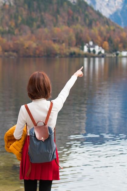 Ragazza asiatica del viaggiatore turistico che sta dito indicante alla libertà di sensibilità del lago pacifica Foto Premium