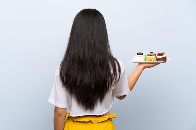 Ragazza asiatica dell'adolescente che tiene i lotti di mini torte differenti nella posizione posteriore Foto Premium