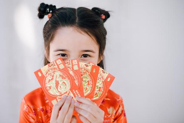 Ragazza asiatica felice del nuovo anno cinese che tiene le buste rosse Foto Premium