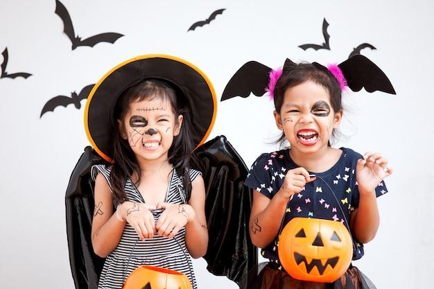 Ragazza asiatica felice del piccolo bambino in costumi e trucco divertendosi sulla celebrazione di halloween Foto Premium