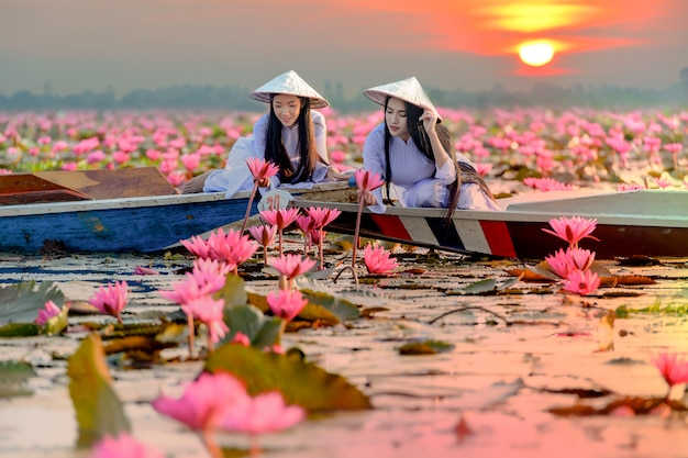 Ragazza asiatica in costume nazionale del vietnam che si siede sulla barca nel mare di loto rosso in undon thani, tailandia. Foto Premium
