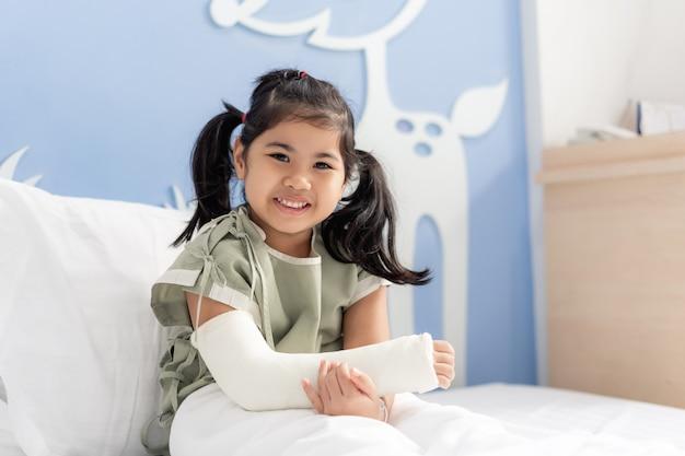 Ragazza asiatica in ospedale sdraiato nel letto con un braccio rotto indietro dalla chirurgia Foto Premium