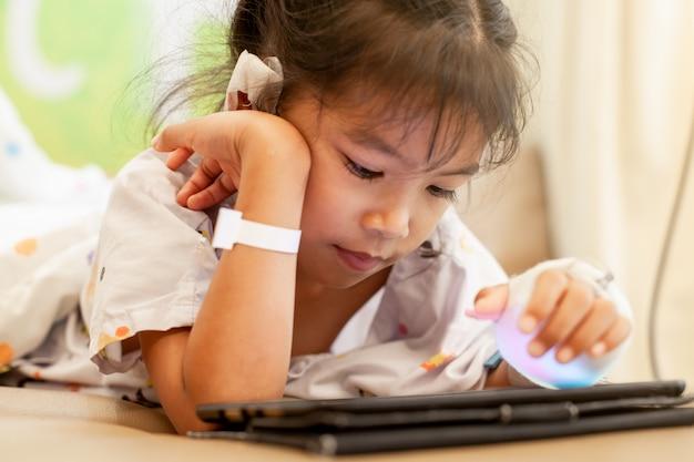 Ragazza asiatica malata del piccolo bambino che ha soluzione iv bendata che gioca compressa digitale Foto Premium