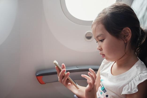 Ragazza asiatica mista utilizzando smart phone in volo, famiglia che viaggia all'estero con i bambini Foto Premium
