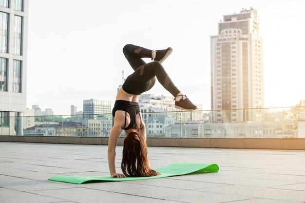 Ragazza atletica impegnata in atletica leggera in città, si allena al mattino per strada, una donna fa un esercizio al tramonto Foto Premium