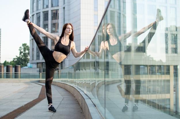 Ragazza atletica impegnata in atletica leggera sullo sfondo della città, si allena al mattino per strada, una donna fa stretching e trucchi di ginnastica Foto Premium
