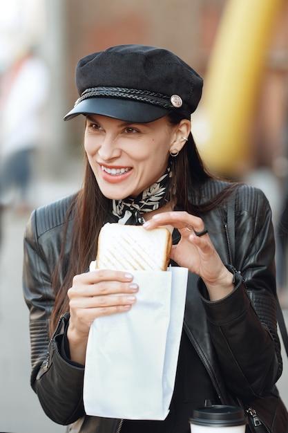 Ragazza attraente che mangia panino per strada Foto Premium