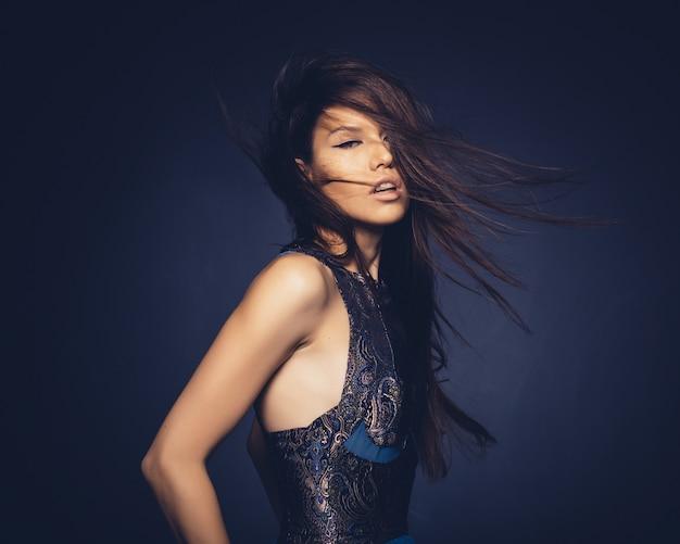 Ragazza attraente con i capelli di volo che posano nello studio Foto Gratuite