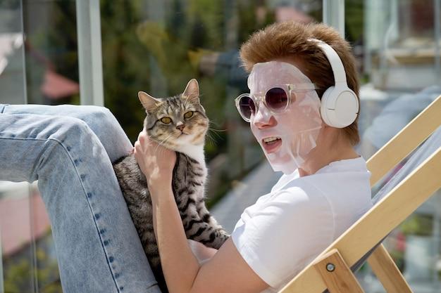 Ragazza attraente con l'acconciatura alla moda che applica maschera facciale sul viso, giocando con il gatto e ascoltando musica. Foto Premium