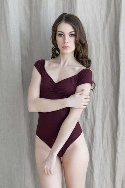 Ragazza attraente del brunette che propone in un vestito di bodie su una priorità bassa grigia del tessuto. luce naturale dalla finestra Foto Premium